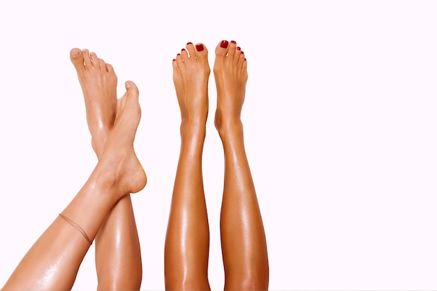 Two beautiful pairs of smooth womans legs after laser hair removal on the white background
