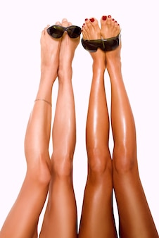 Two beautiful pairs of smooth womans legs after laser hair removal with protection glasses