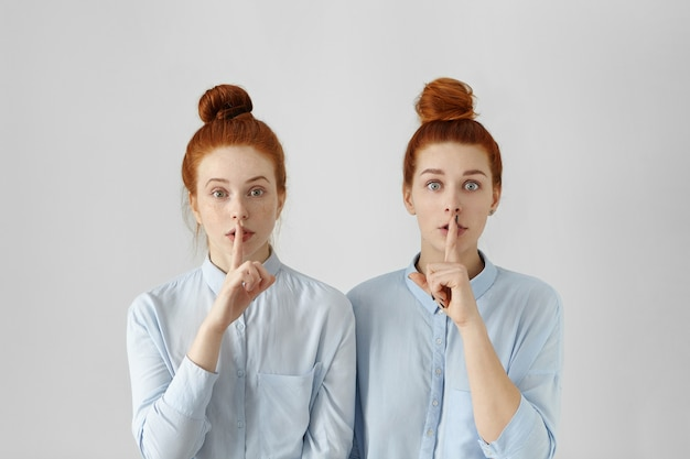 Due belle donne rosse con gli stessi capelli, vestite con identiche camicie formali