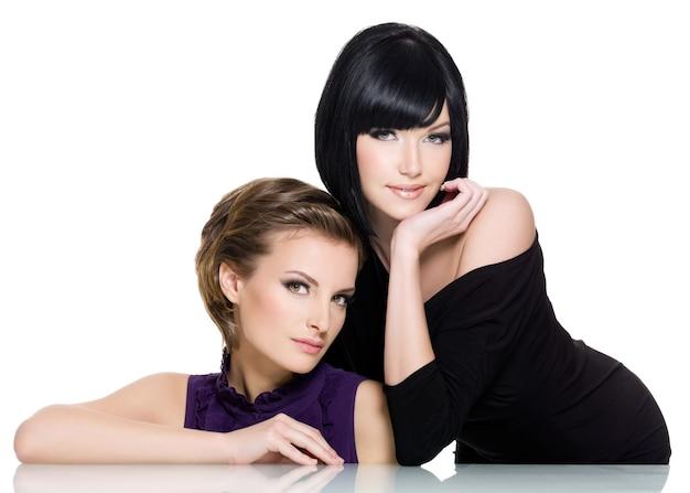 白で隔離される2人の美しいセクシーな魅力の若い女性