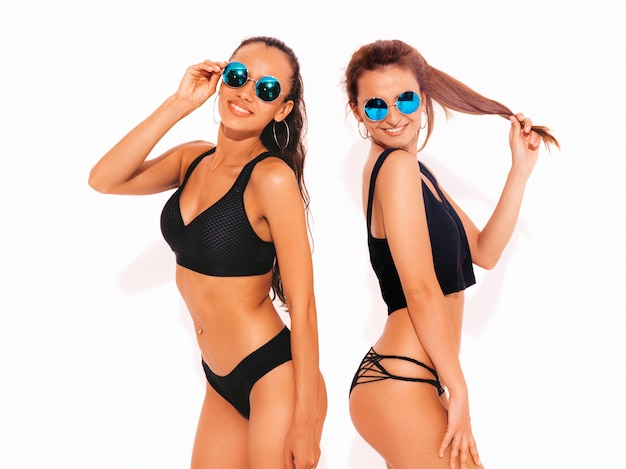 Two beautiful sexy smiling women in black lingerie. trendy hot models having fun. girls isolated in sunglasses