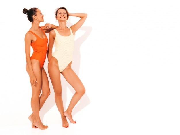 夏のカラフルな赤と黄色の水着水着で2人の美しいセクシーな笑顔の女性。楽しいトレンディなホットモデル。分離された女の子
