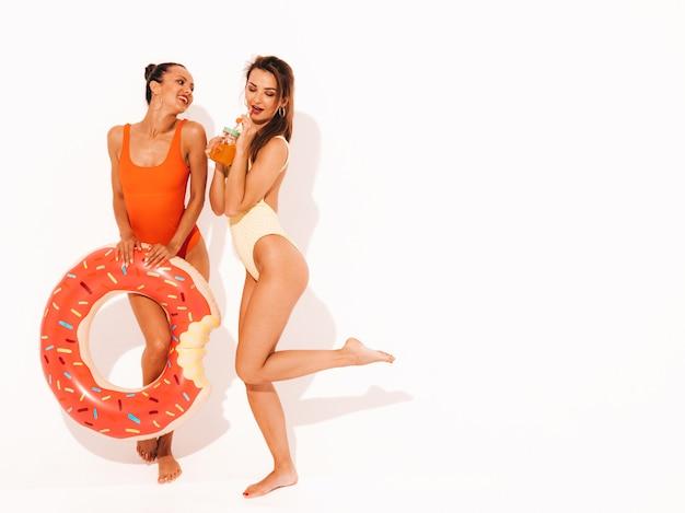 夏のカラフルな水着水着で2人の美しいセクシーな笑顔の女性。分離された女の子。ドーナツリロインフレータブルマットレスと新鮮なカクテルスムージードリンクを飲んで面白いモデル