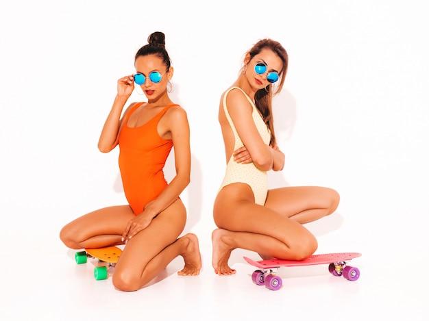 Две красивые сексуальные улыбающиеся женщины в летних разноцветных купальниках. модные девушки в солнечных очках. позитивные модели сидят на полу с разноцветными копеечными скейтбордами. изолированные