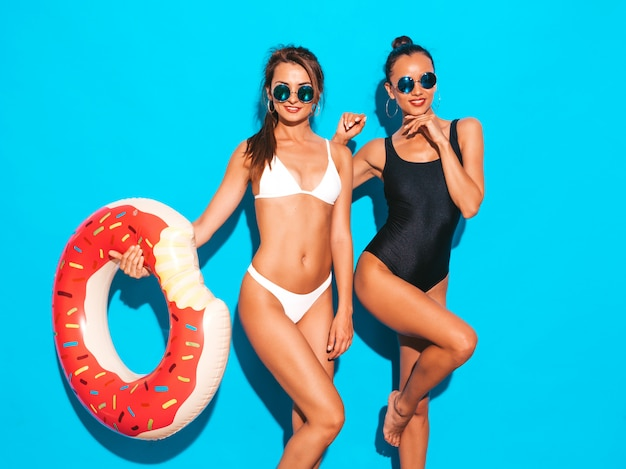 Две красивые сексуальные улыбающиеся женщины в летних белых и черных купальных костюмах. девушки в солнцезащитные очки. позитивные модели с удовольствием надувной матрас пончик lilo.изолированные на синей стене