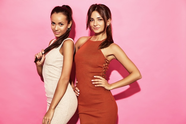 Two beautiful sexy smiling women models wear stylish design trend clothing cotton dress, casual summer style for date meeting walk party. brunette hot businesswoman women posing on pink wall