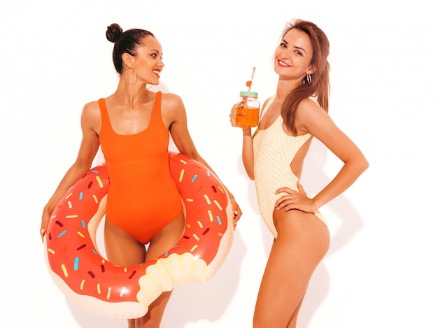 Two beautiful sexy smiling women in summer colorful swimwear bathing suits. girls isolated. funny models drinking fresh cocktail smoozy drink with donut lilo inflatable mattress