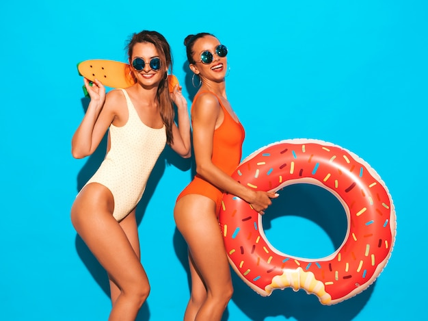 Two beautiful sexy smiling women in summer colorful swimwear bathing suits. girls in sunglasses. positive models having fun with colorful penny skateboard. with donut lilo inflatable mattress