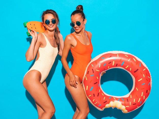 Two beautiful sexy smiling women in summer colorful swimwear bathing suits. girls in sunglasses. positive models having fun with colorful penny skateboards. with donut lilo inflatable mattress