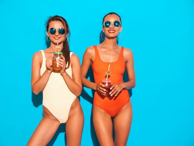 Due belle donne sorridenti sexy in costumi da bagno colorati costumi da bagno estate. ragazze alla moda in occhiali da sole. impazzendo. modelli divertenti isolati. bere cocktail fresco bevanda liscia