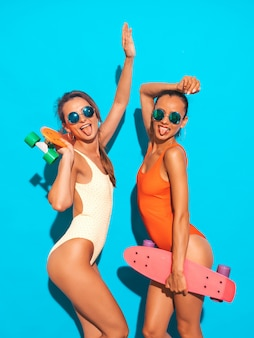 Two beautiful sexy smiling women in summer colorful swimwear bathing suits. trendy girls in sunglasses. positive models having fun with colorful penny skateboards. isolated. shows tongue