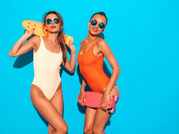 Due belle donne sorridenti sexy in costumi da bagno colorati costumi da bagno estate. ragazze alla moda in occhiali da sole. modelle positive che si divertono con colorati penny skateboard. isolato