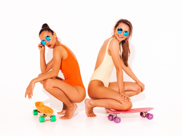 Two beautiful sexy smiling women in summer colorful swimwear bathing suits. trendy girls in sunglasses. positive models sitting on the floor with colorful penny skateboards. isolated