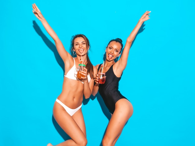 Two beautiful sexy smiling women in summer white and black swimwear bathing suits.girls going crazy.funny models isolated on blue.drinking fresh cocktail smoozy drink.raising their hands