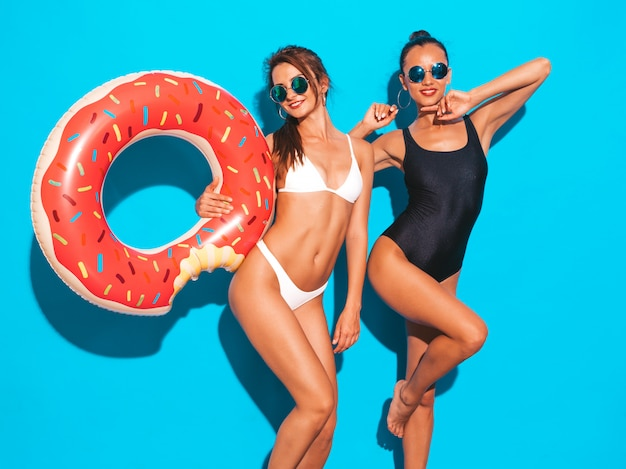 Two beautiful sexy smiling women in summer white and black swimwear bathing suits.girls in sunglasses. positive models having fun with donut lilo inflatable mattress.isolated on blue wall