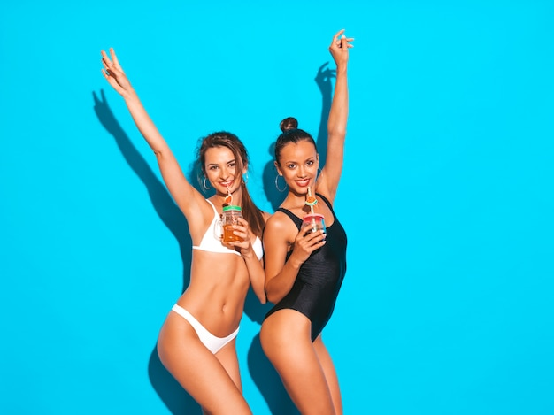 Two beautiful sexy smiling women in summer white and black swimwear bathing suits.trendy girls going crazy.funny models isolated on blue.drinking fresh cocktail smoozy drink.raising hands