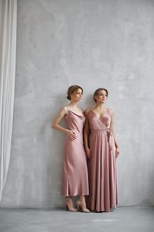 ライトベージュのシルクのドレスを着た2人の美しいセクシーな女性。
