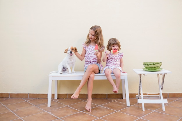 Two beautiful sister kids eating a watermelon ice cream with their cute dog. family love and lifestyle outdoors