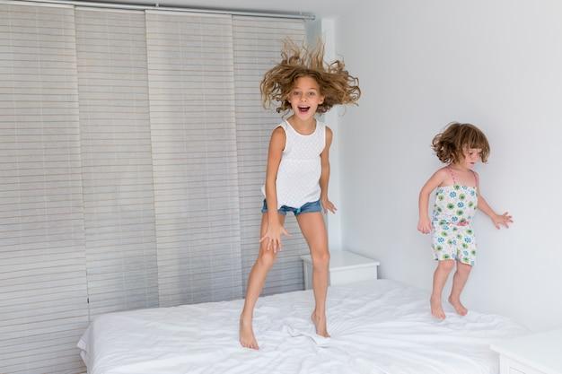 2つの美しい姉妹の子供たちが遊んで、自宅のベッドでジャンプします。屋内で楽しい。家族の愛とライフスタイル