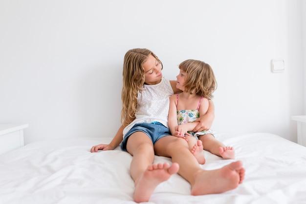 自宅のベッドで遊ぶ2人の美しい姉妹の子供。