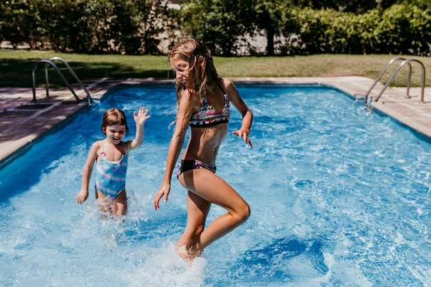 Two beautiful sister kids at the pool playing, running and having fun outdoors. summertime and lifestyle concept
