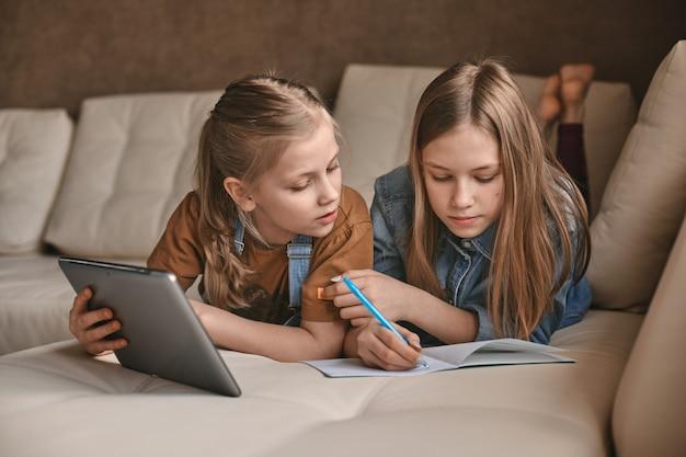 検疫中に2人の美しい姉妹が宿題をします。子供たちはガジェットを使って学習します。