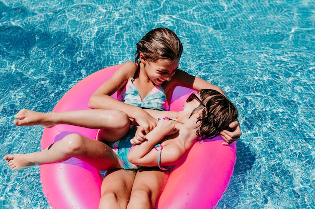 Two beautiful sisters floating on pink donuts in a pool. playing tickles and smiling. fun and summer lifestyle