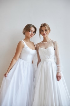 Two beautiful slender woman in white wedding dress, new collection of dresses for the bride. noise, out of focus