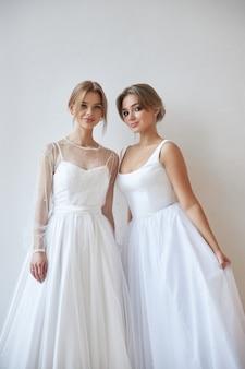 Two beautiful slender woman in white wedding dress