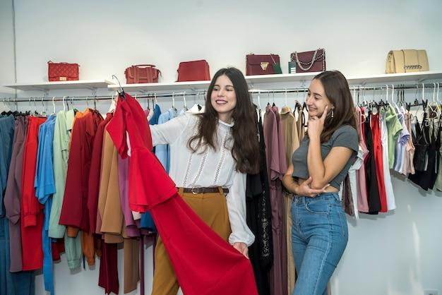 衣料品小売店で選んで買い物をしている2人の美しい笑顔の友達。ブラックフライデー