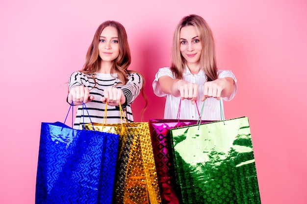 Two beautiful and smiling female person (mother and daughter) holding a lot of shopping bags on a pink background in the studio. concept of sale and shopping