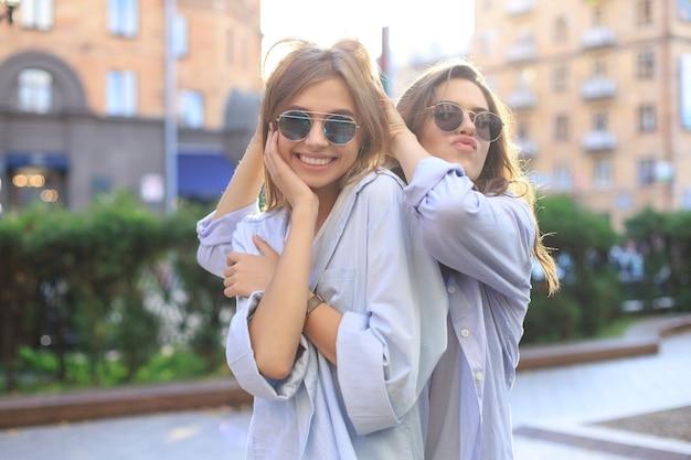 거리 배경에서 포즈를 취하는 트렌디한 여름 옷을 입은 두 명의 아름다운 웃는 소녀. 모델들이 즐겁게 포옹하고 있습니다.