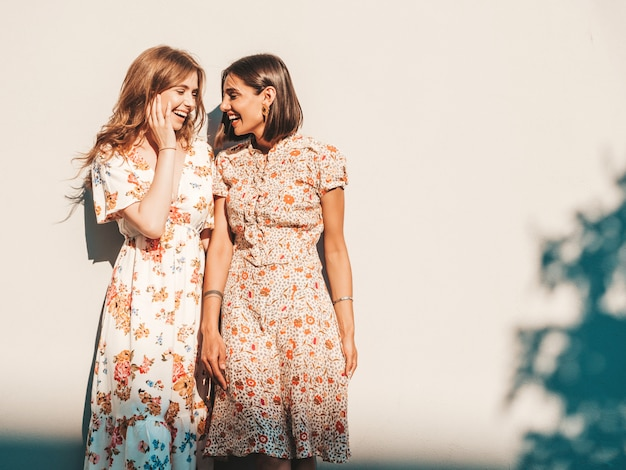 Two beautiful smiling girls in trendy summer sundress posing on the street