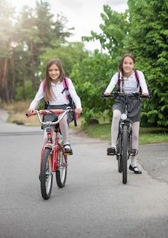 自転車で学校に乗る2人の美しい笑顔の女子学生