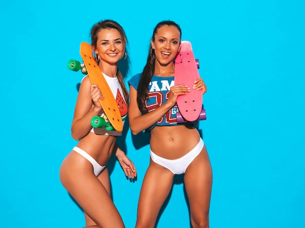 Two beautiful smiling sexy women in summer underpants and topic. trendy girls. positive models having fun with colorful penny skateboards. isolated