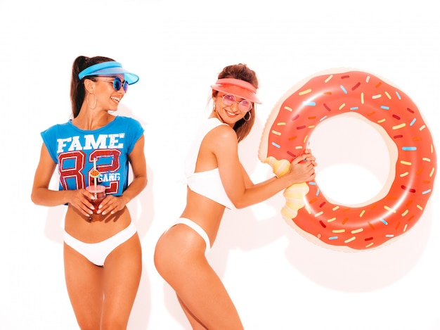 Two beautiful smiling sexy women in white summer underpants and topic. girls in sunglasses,transparent visor cap. models drinking fresh cocktail smoozy drink with donut lilo inflatable mattress