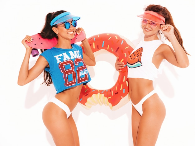Two beautiful smiling sexy women in white summer underpants and topic. girls in sunglasses,transparent visor cap. positive models having fun with donut lilo inflatable mattress. isolated