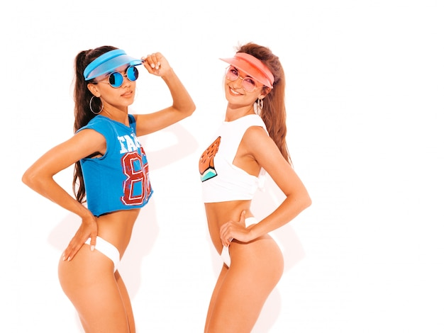 Two beautiful smiling sexy women in white summer underpants and topic. girls in sunglasses and transparent visor cap. trendy models having fun. isolated on white