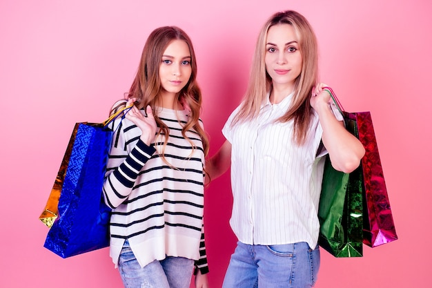Two beautiful and smiling women girlfriends holding many shopping bags on a pink background in the studio. concept of sale and shopping