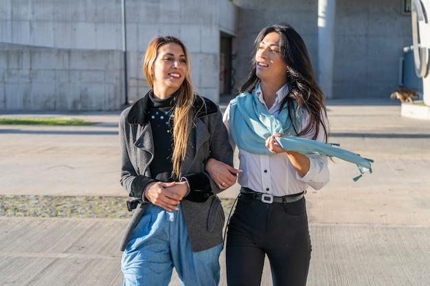 두 명의 아름다운 웃는 여성이 도시 환경을 걸으면서 이야기하고 있습니다. 기쁨과 행복 개념입니다.