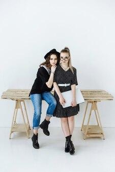 ラップトップを手に持って、テーブルに座ってポーズをとる2人の美しいスタイリッシュな女性モデル