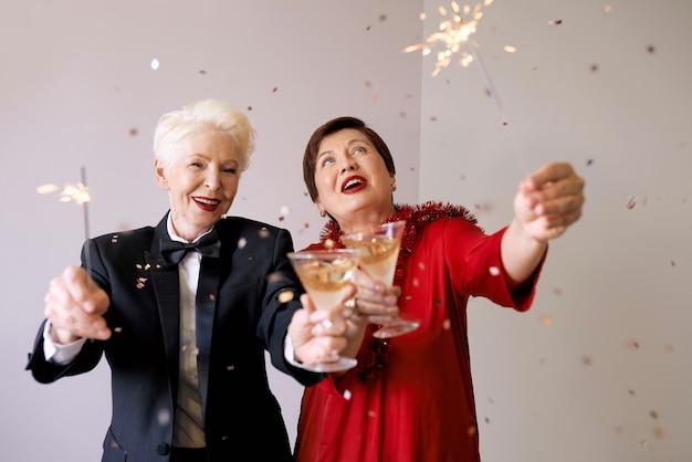 Two beautiful stylish mature senior women celebrating new year