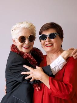 Две красивые стильные зрелые пожилые женщины в солнцезащитных очках обнимаются