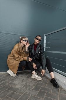 검은색 청바지와 신발을 신은 세련된 가죽 재킷에 빈티지 선글라스를 착용한 두 명의 아름다운 세련된 모델 소녀가 거리의 금속 어두운 벽 근처에 앉아 있습니다