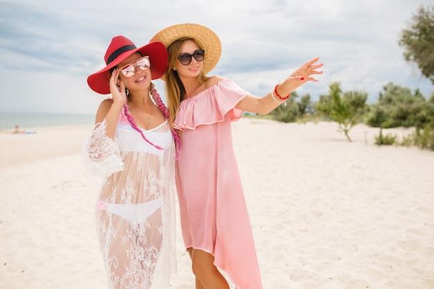Две красивые стильные женщины на пляже на отдыхе, летний стиль,