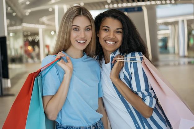 쇼핑 가방을 들고 카메라를보고 쇼핑 센터에서 웃고 두 아름다운 세련된 여성