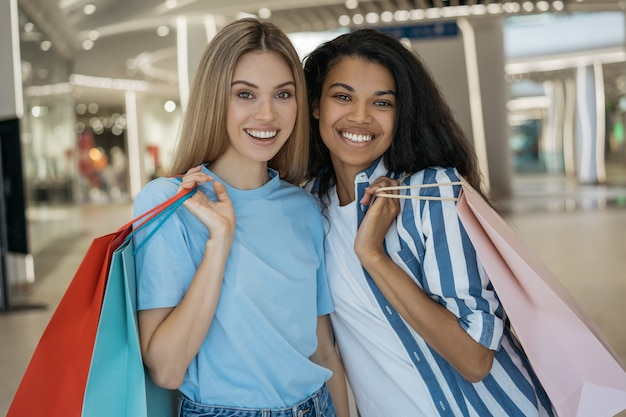 Two beautiful stylish women holding shopping bags, looking at camera and smiling in shopping centre