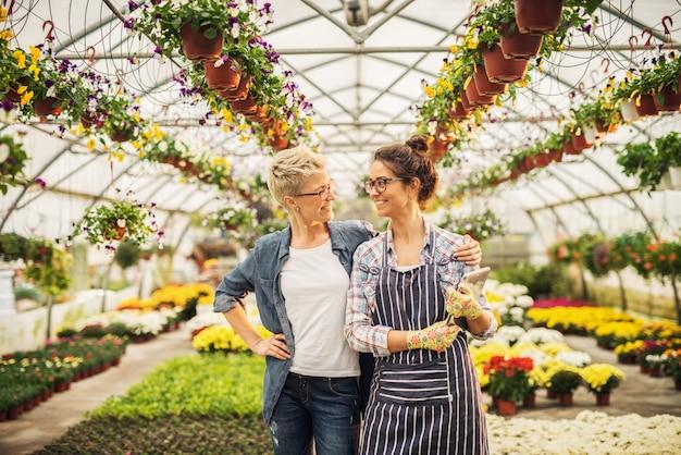 色とりどりの花が咲く温室に誇りを持って立っている2人の美しい花屋。