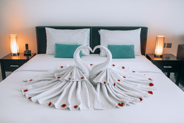 Two beautiful swans made of towels located on a white bed with rose cakes
