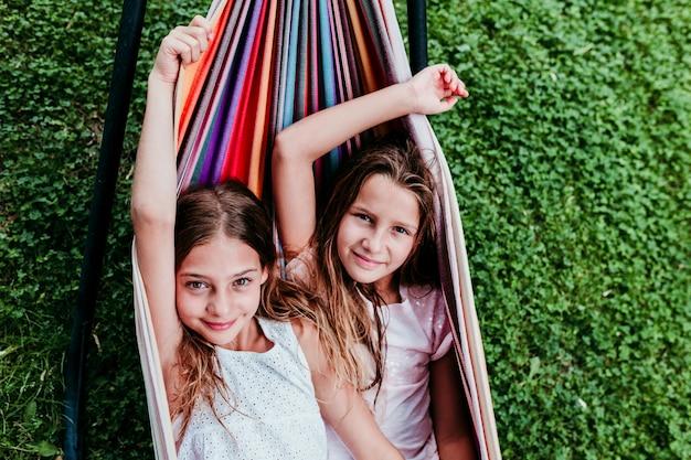 庭でカラフルなハンモックに横たわっている2つの美しい10代の女の子。カメラを見て、ライフスタイル、リラックスして楽しいアウトドア